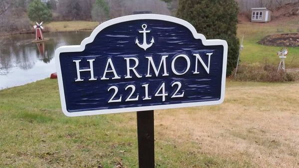 Navy blue and white sign with anchor, family name, and house number