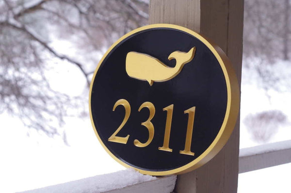 Side view of custom carved oval house number with whale image