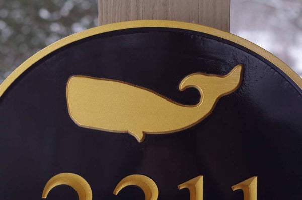 close up of custom carved oval house number with whale image