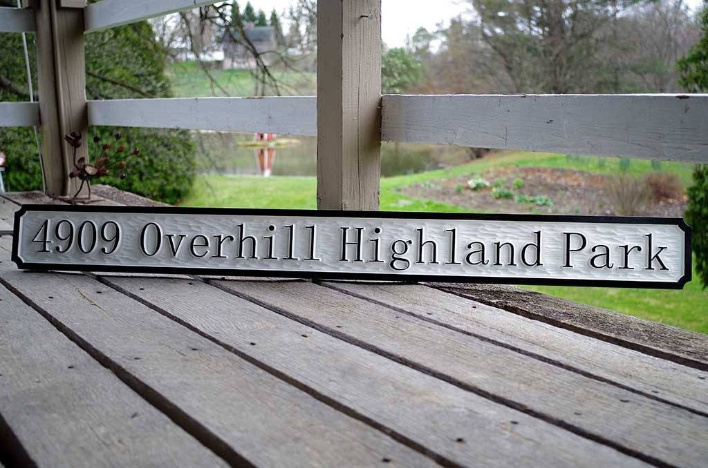 Address sign with 4909 Overhill Highland Park carved on it and painted black and white