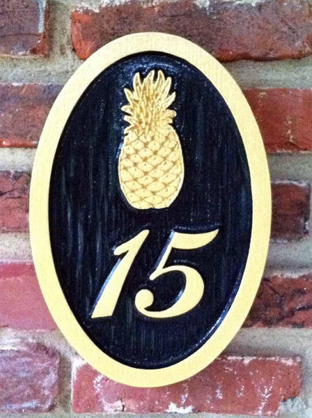 Custom carved house number address sign with a pineapple and 15 oval shape painted black and gold