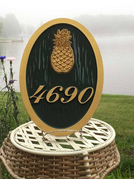 Custom carved house number address sign with a pineapple oval shape painted green and gold