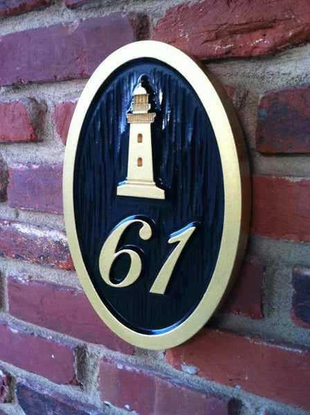 Custom carved house number address sign with a lighthouse and 61 oval shape painted black and gold