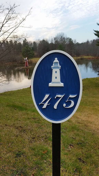 Custom carved house number address sign with a lighthouse and 475 oval shape painted blue and white