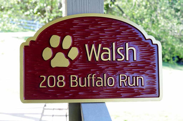 Custom carved address sign with family name and paw print image painted red and gold