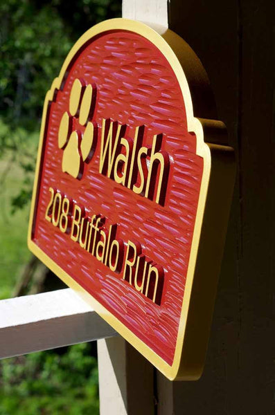 side view of Custom carved address sign with family name and paw print image painted red and gold