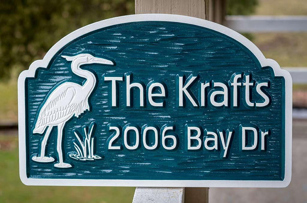 Custom carved address sign with family name and bleu heron image painted green and white
