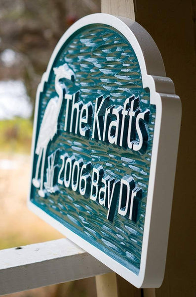 side view of Custom carved address sign with family name and bleu heron image painted green and white
