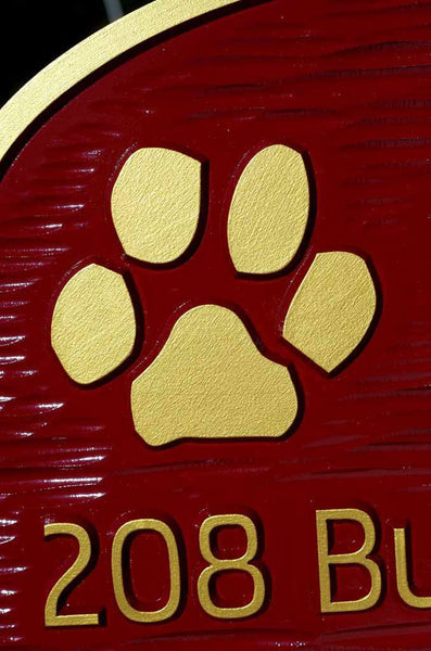 close up of paw print on Custom carved address sign with family name painted red and gold