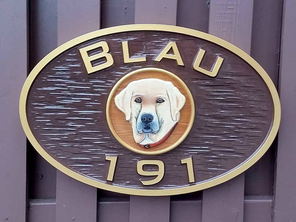 Oval last name and house number sign with yellow labrador retriever