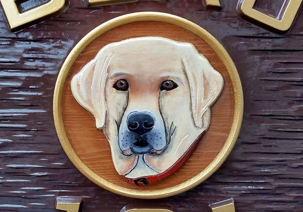 Oval last name and house number sign with yellow labrador retriever close up
