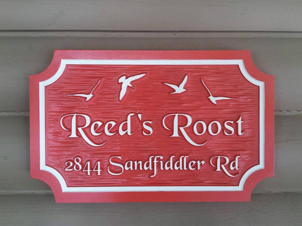Custom carved house name sign with house number and seagulls carved on it