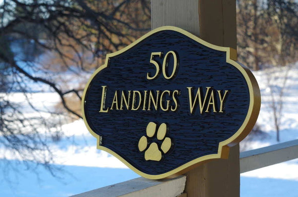 Custom carved address sign with paw print painted black and gold