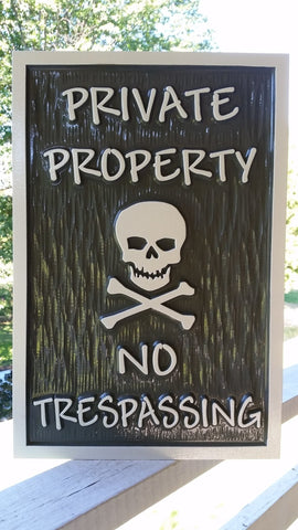 Private property no trespassing sign with skull and cross bones