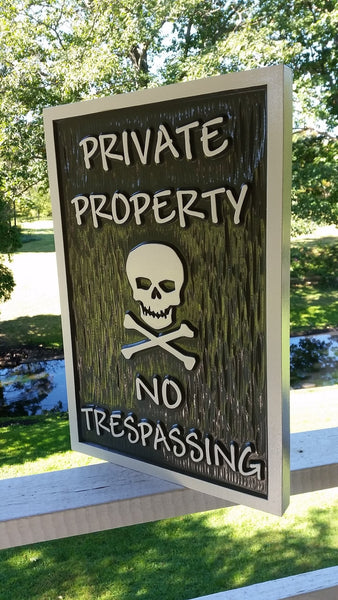 Private property no trespassing sign with skull and cross bones dark and light gray color scheme