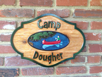 Rustic cedar carved camp sign with last name and canoe on lake image