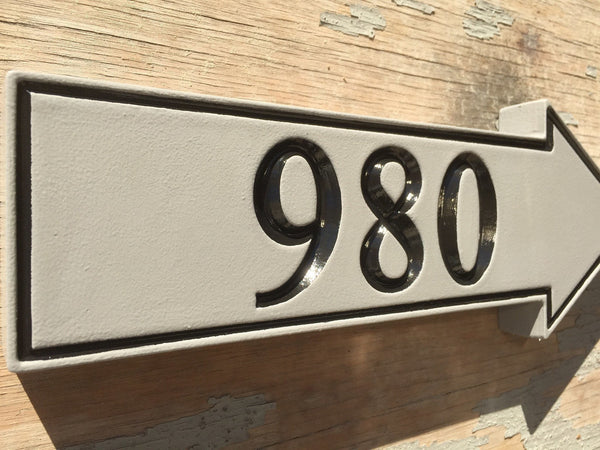 angle view of house number sign gray and black custom carved arrow pointing right