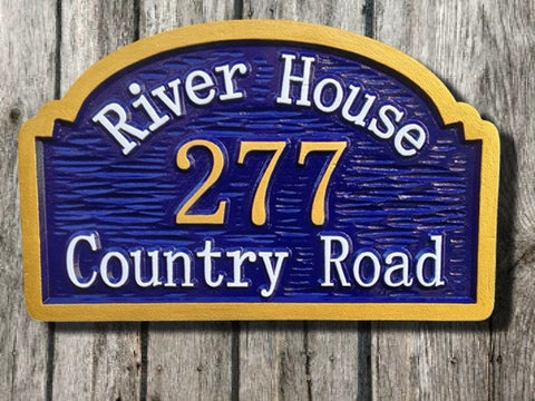 Personalized carved address sign that says River House with arch top painted blue gold and white