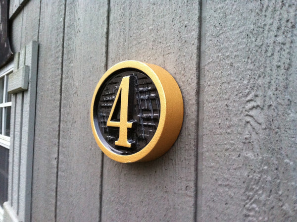 Oval house number sign with cross hatch textured background -iso