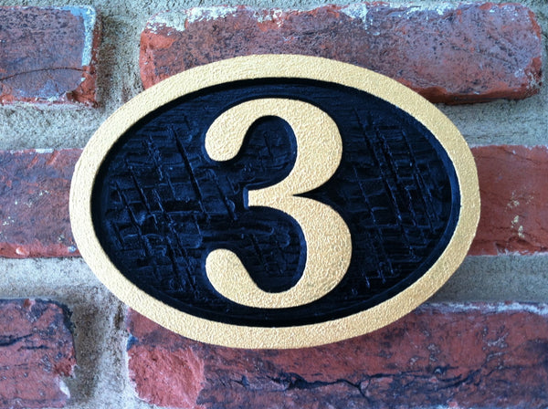 Oval house number sign with cross hatch textured background -front