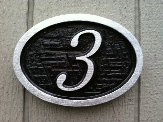 Oval house number sign with cross hatch textured background -front2