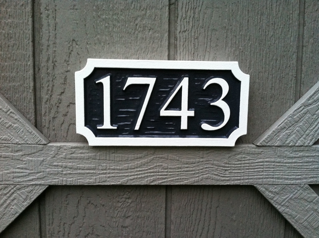 House number sign with textured background painted black and white