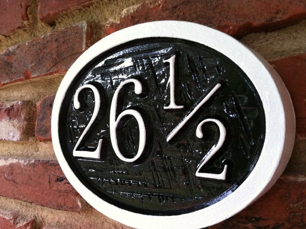Oval house number sign with half number and cross hatch texture