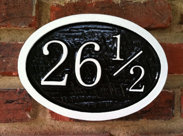 Oval house number sign with half number and cross hatch texture -front
