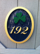 3 digit house number with fancy font and green shamrock easy to read black and gold color scheme