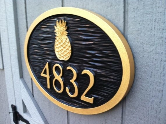 side view of carved house number sign with pineapple painted black and gold