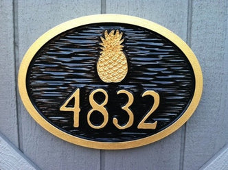 carved house number sign with pineapple painted black and gold