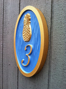 Bright blue and gold house number sign
