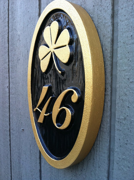 Custom carved house number address sign with a shamrock and 46 oval shape painted black and gold