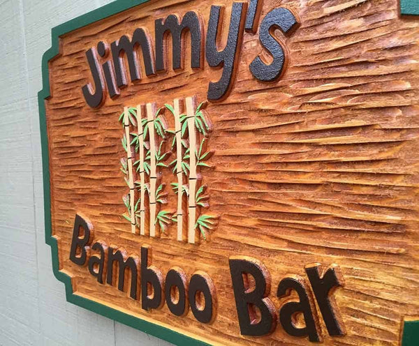 Custom carved rectangle cedar bar sign with name and bamboo image side view
