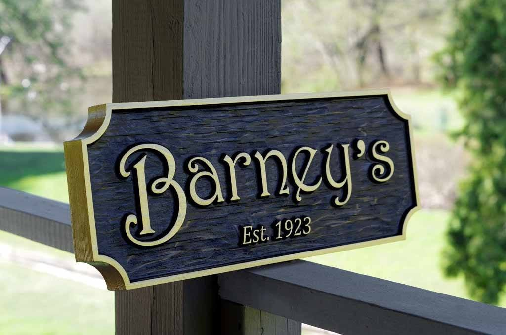 Custom Carved Cedar bar sign with black stain and Barney's carved on it with Est. year