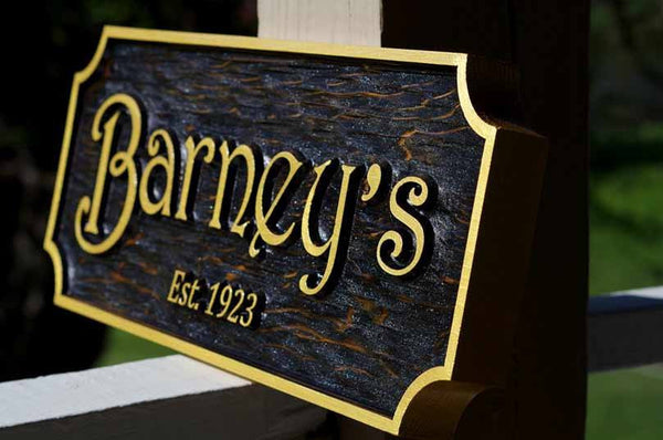 Side view of Custom Carved Cedar bar sign with black stain and Barney's carved on it with Est. year