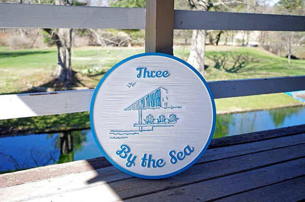 Three by the Sea carved sign in white and sky blue with gazebo image