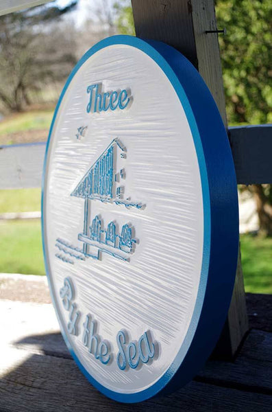 Side view of Three by the Sea carved sign in white and sky blue with gazebo image