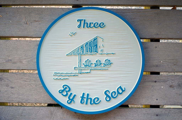 Three by the Sea custom carved sign in white and sky blue with gazebo image