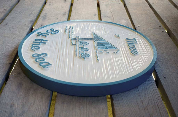 Three by the Sea carved sign in white and sky blue with gazebo image Side view