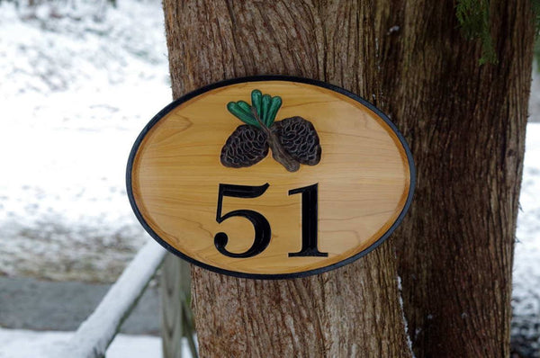 Custom carved cedar sign with pinecone image