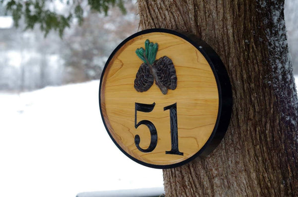 Side view of custom carved cedar wood house number sign with pinecone