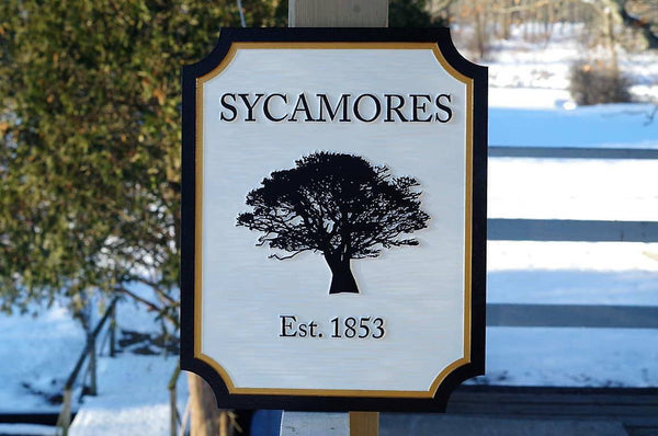 Black and white entrance sign with sycamore tree and established date