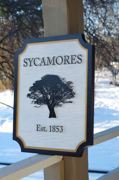 Side view of entrance sign with sycamore tree and established date