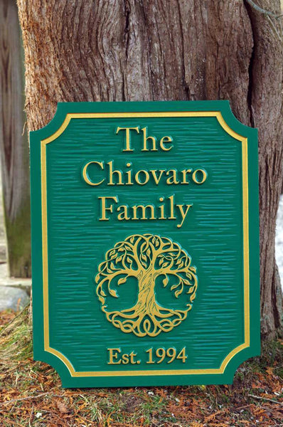 Custom carved entrance sign with tree and established date painted green and gold