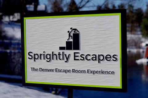 Sprightly Escapes carved business sign painted white, lime green and black border