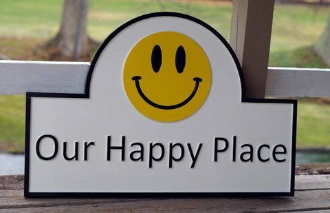 Our Happy Place carved sign with arched top and yellow smiley face image
