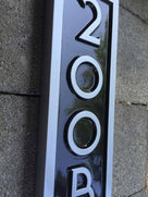 Vertical house number sign with letter