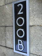 Side view of vertical custom made address number with letter rectangular sign painted black and silver
