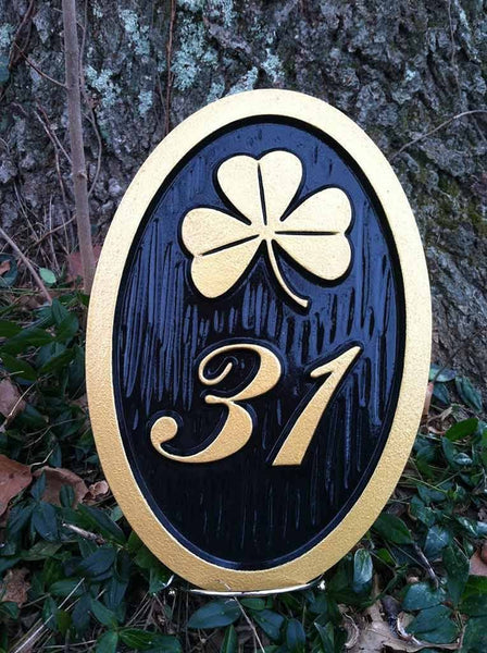 Custom carved house number address sign with a shamrock and 31 oval shape painted black and gold